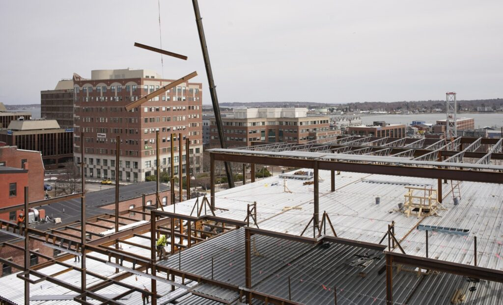 Iron beams are swung into place over a six-story apartment development on Free Street in Portland on Wednesday. For the most part, work is continuing on construction projects in Maine, although companies are taking precautions to protect workers from coronavirus exposure.