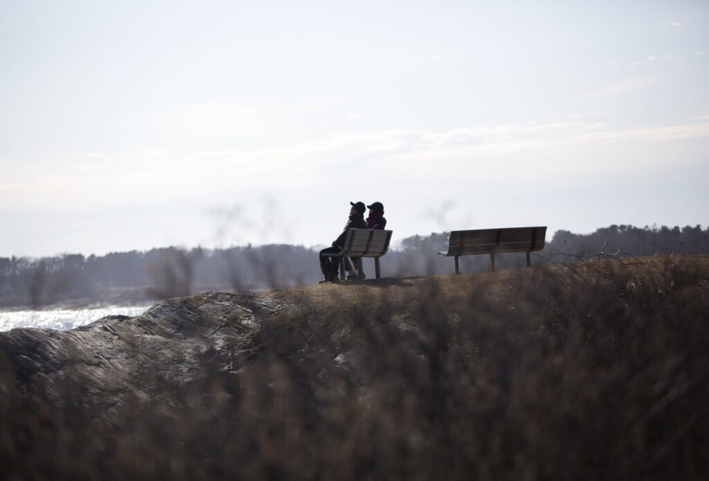 A couple sit on a bench at Kettle Cove State Park on Thursday, March 26, 2020.