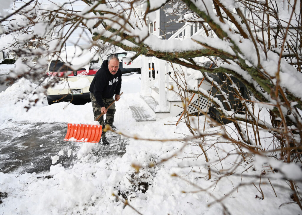 Esi Mohbiti of Maple Street in Saco shovels off his walkway after the overnight snowfall.