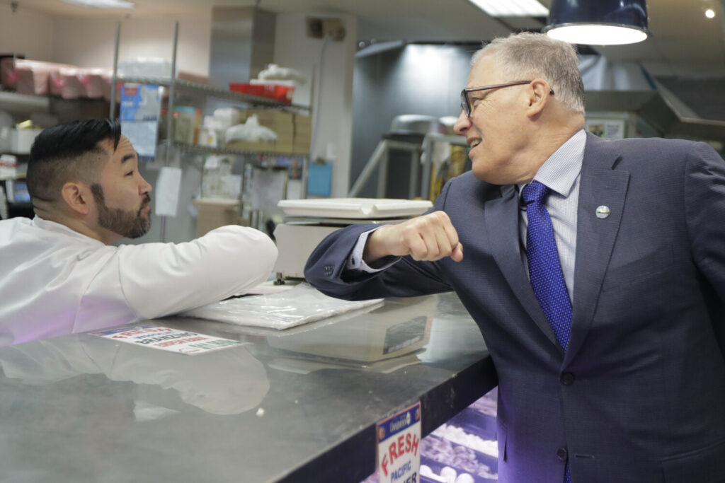 Washington Gov. Jay Inslee, right, bumps elbows with a worker at a Seattle food store.