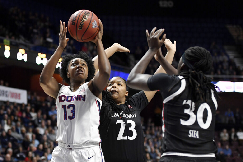 Connecticut's Christyn Williams shoots over Cincinnati's IImar'I Thomas, center, and Florence Sifa during the Huskies' 87-53 win in the American Athletic Conference final on Monday.