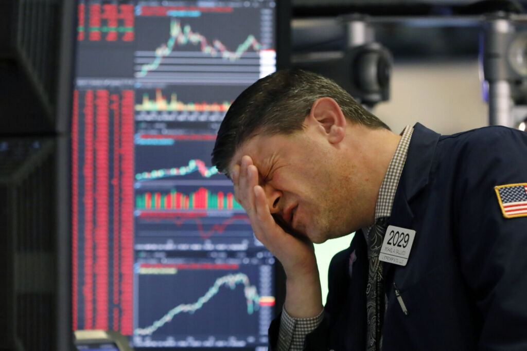 Trader Michael Gallucci works at his post on the floor of the New York Stock Exchange on Wednesday. The Dow industrials closed down 1,465 points, or 5.9%, as investors wait for a more aggressive response from the U.S. government to economic fallout from the coronavirus.