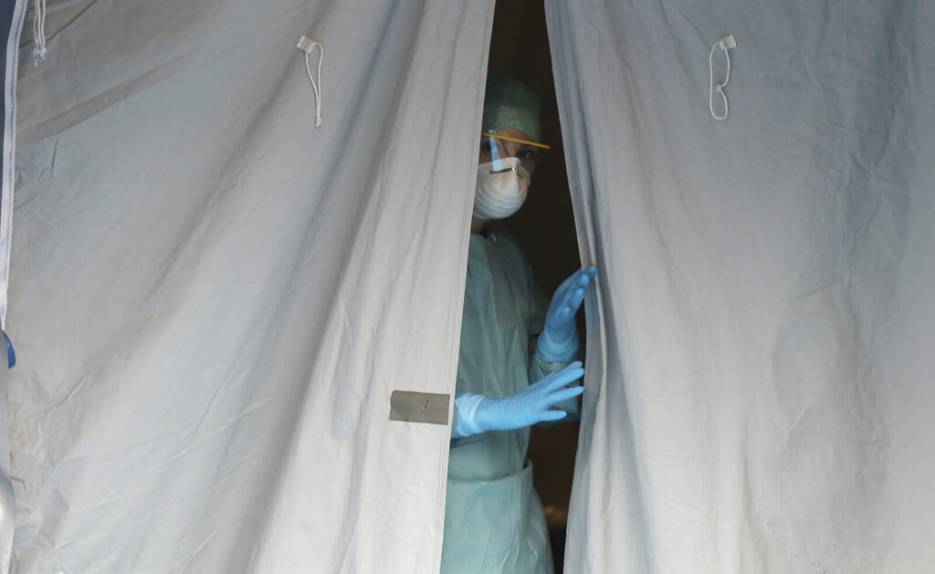 A medical staffer watches from a tent Thursday at one of the emergency structures that were set up to ease procedures at the Brescia hospital in northern Italy. Italians woke up to yet further virus-containment restrictions after Premier Giuseppe Conte ordered restaurants, cafes and retail shops closed after imposing a nationwide lockdown on personal movement.