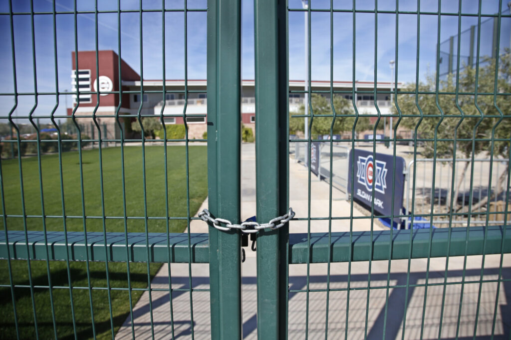 A gate at the Chicago Cubs practice facility at Sloan Park in Mesa, Ariz., is closed and locked Monday. Major League Baseball expects Opening Day to be delayed until mid-May at the earliest after the CDC recommended gathers of 50 people or more be postponed or delayed for eight weeks.