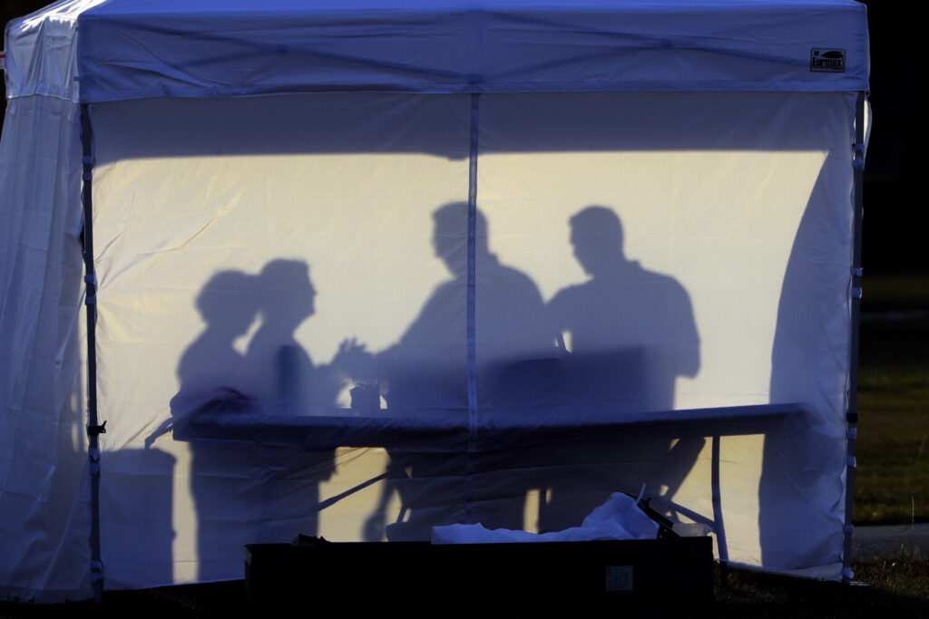 Medical personnel are silhouetted against the back of a tent before the start of coronavirus testing in the parking lot outside of Raymond James Stadium early Wednesday in Tampa.