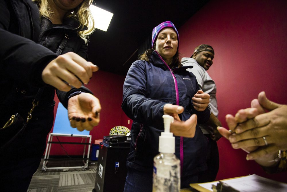 Sharon Trask and other voters use hand sanitizer as they stand in line to vote at Lincoln Lodge Polling station in Chicago's 1st ward on Tuesday. Election officials promoted voting early and casting ballots by mail in an attempt to control crowds and curb the spread of coronavirus.