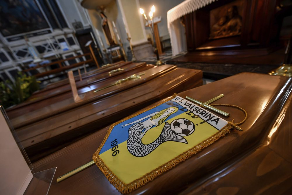 Coffins, one of them with the pennant of the local soccer team, wait in a church to be transported to a cemetery in Serina,  Northern Italy, on Saturday. Claudio Furlan/LaPresse via AP