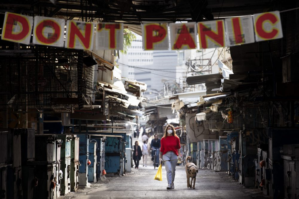 "A woman walks her dog under a ""don't panic"" sign hanging on the entrance of a food market that was shut down Monday in Tel Aviv, Israel."