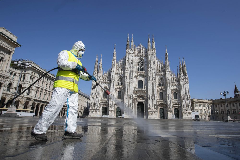 A worker sprays disinfectant to sanitize Duomo square, as the city's main landmark, the Gothic cathedral, stands out in background, in Milan, Italy, on Tuesday.