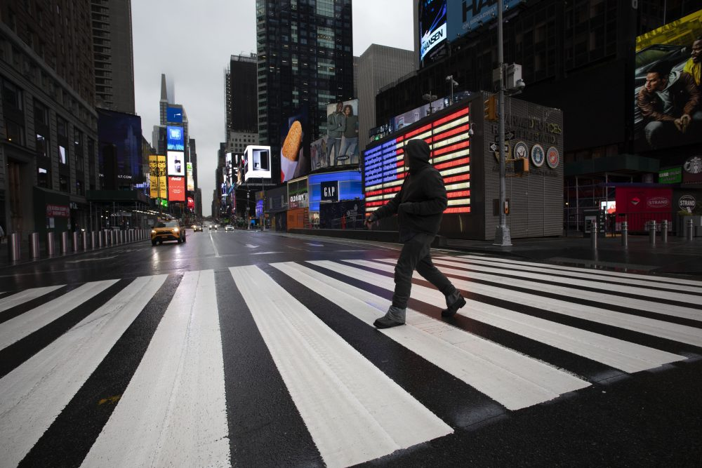 A man crosses the street in a nearly empty Times Square, which is usually very crowded on a weekday morning, on Monday in New York. Gov. Andrew Cuomo has ordered most New Yorkers to stay home from work to slow the coronavirus pandemic.