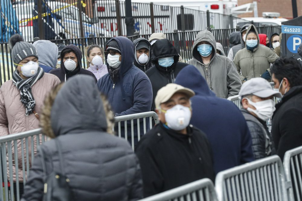 Patients wear personal protective equipment while maintaining social distancing as they wait in line for a COVID-19 test at Elmhurst Hospital Center on Wednesday in New York.