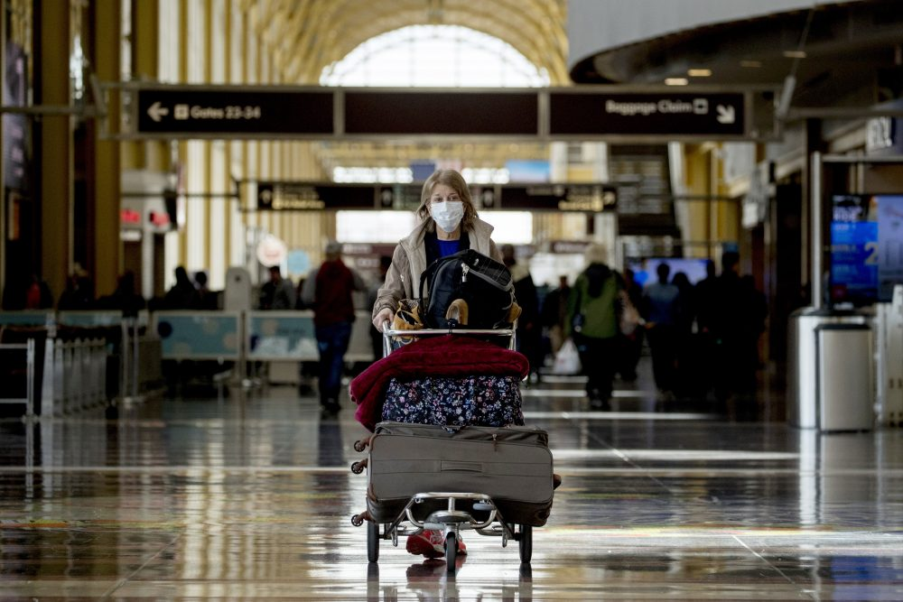 A woman wearing a mask walks through a terminal at Ronald Reagan Washington National Airport on Monday in Arlington, Va.