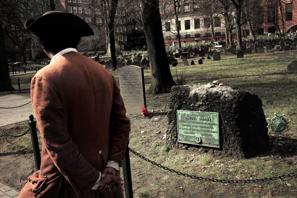 Samuel Ike, of Cambridge, Mass., dressed as Revolutionary War-era African American abolitionist Prince Hall, walks past the grave for victims of the Boston Massacre, left, and for founding father Samuel Adams, right, at the Granary Burying Ground in Boston. On March 5, 1770, British soldiers opened fire on a crowd, klling five people.