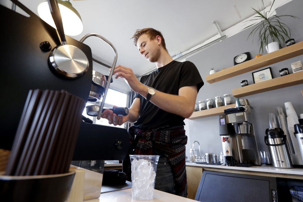 Barista Porter Hahn makes a drink for a customer in a coffee shop Nov. 4 in Seattle. U.S. services companies grew at a faster pace in February 2020 than the previous month, an indication that the economy is still expanding, despite growing concerns about global coronavirus outbreak.