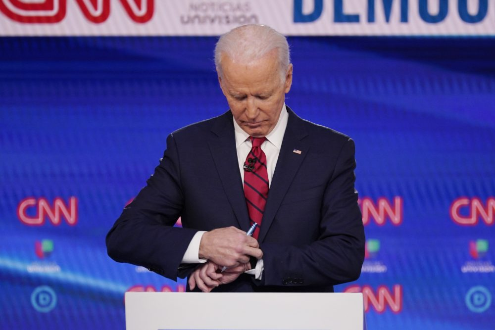 Former Vice President Joe Biden check his watch during a commercial break as he participates in a Democratic presidential primary debate Sunday at CNN Studios in Washington.