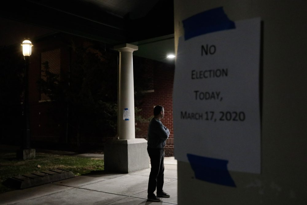 A man, who hoped to vote in the scheduled primary election Tuesday, stands outside a closed polling station at Schiller Recreation Center in Columbus, Ohio. U.S. elections have been upended by the coronavirus pandemic. At least 13 states have postponed voting and more delays are possible as health officials warn that social distancing and other measures to contain the virus might be in place for weeks, if not months.