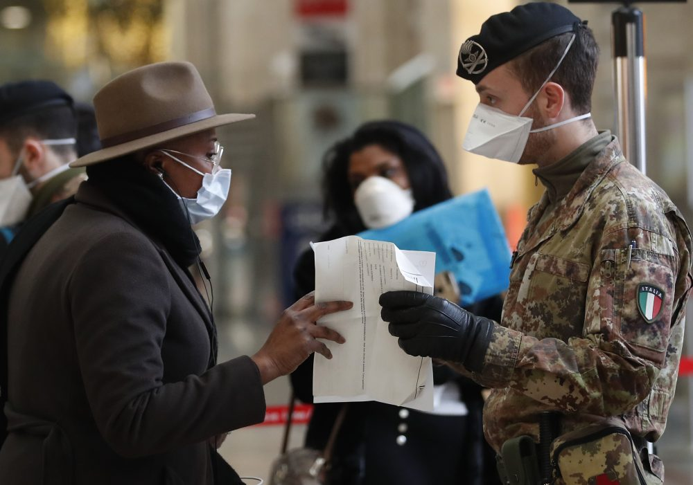 Italian police officers and soldiers check passengers leaving from Milan's main train station on Monday.