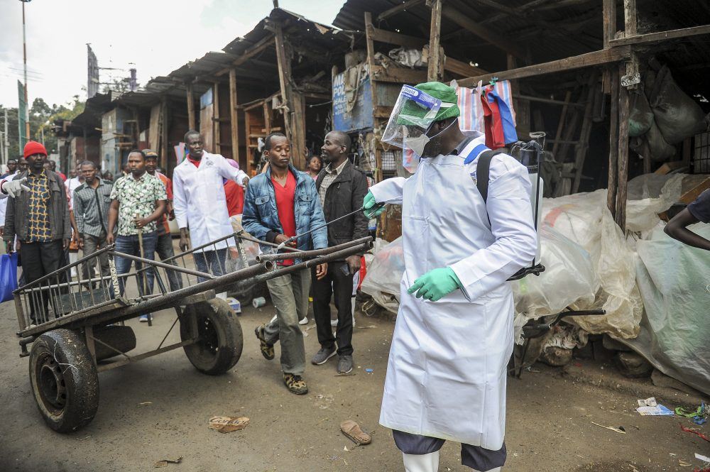 A Kenyan Health Ministry official sprays disinfectant onto a hand-cart to control the spread of the coronavirus in a outdoor street market in Nairobi. John Muchucha/Associated Press