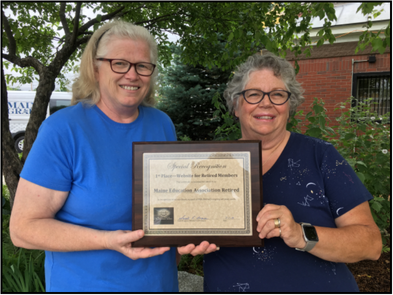 Communications Committee Chairperson Jane Conroy of Dover-Foxcroft, left, congratulates Web Administrator Pam Partridge of North Anson for her work in earning national recognition, First Place With Distinction.