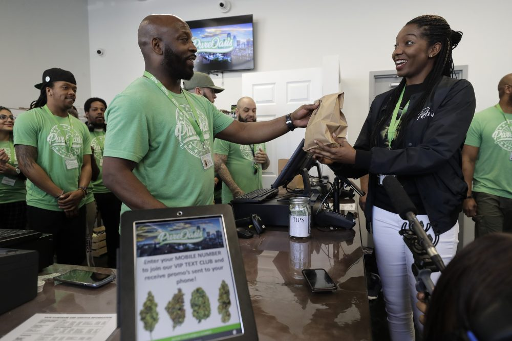 Kevin Hart, front left, co-owner of Pure Oasis recreational marijuana shop, completes a sale of cannabis products to the store's first customer, Niambe McIntosh, moments after the store opened for the first time on Monday in Boston. Pure Oasis is Boston's first recreational marijuana shop.