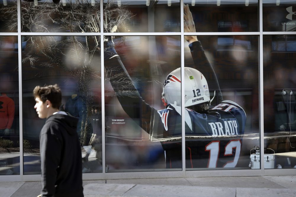 A passer-by walks past an oversized photograph of former New England Patriots football quarterback Tom Brady last week at Patriot Place mall, in Foxborough, Mass. Brady left the Patriots after 20 years and six Super Bowl title last week.