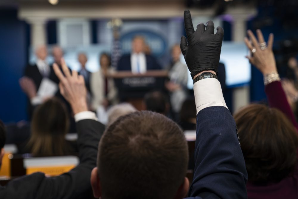 Reporters raise their hands to ask President Trump questions during a press briefing March 16 with the coronavirus task force, at the White House in Washington.