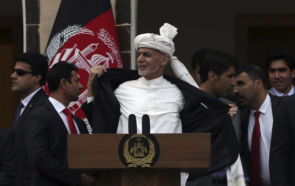 Afghan President Ashraf Ghani, center, opens his coat after a few rockets are fired during his speech at his inauguration ceremony  in Kabul on March 9. To reassure his supporters, Ghani threw open his jacket saying he wasn't even wearing a bulletproof vest. The start of Taliban prisoner releases, planned Saturday to jump-start peace talks, has been postponed. Rahmat Gul/Associated Press