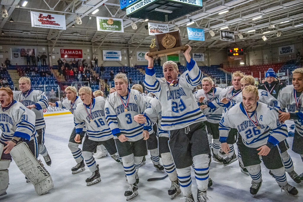 The Lewiston boys ice hockey team celebrates after its Class A State championship win over Scarborough on Saturday at the Androscoggin Bank Colisee.