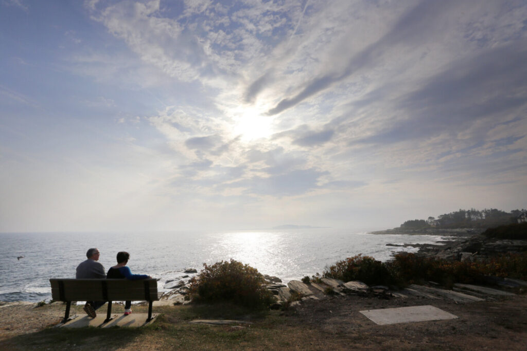 A couple looks out over the Atlantic Ocean from a bench at Two Lights State Park as the sun pokes through the clouds last year. Two Lights is among the parks and beaches that will remain closed at least until June 1.
