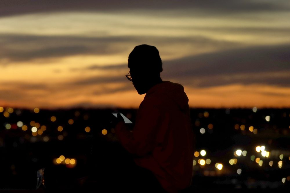 A person looks at a phone as the sun sets, in Kansas City, Mo.