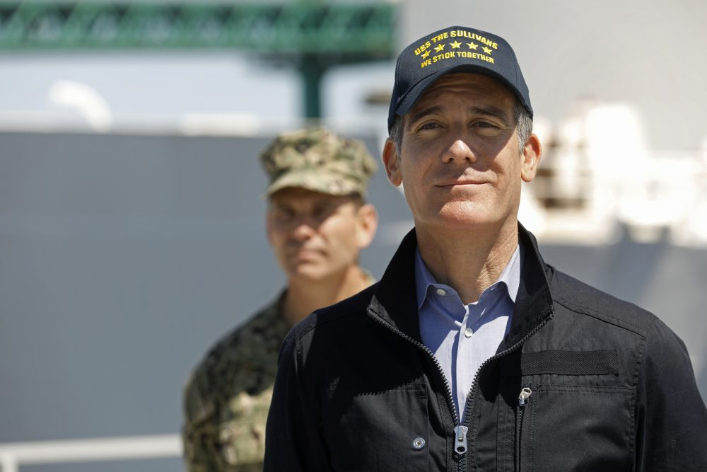Los Angeles Mayor Eric Garcetti listens as California Gov. Gavin Newsom speaks in front of the Navy hospital ship Mercy that arrived at the Port of Los Angeles on Friday to provide relief for Southland hospitals overwhelmed by the coronavirus pandemic. Adm. John Gumbleton is behind Garcetti.