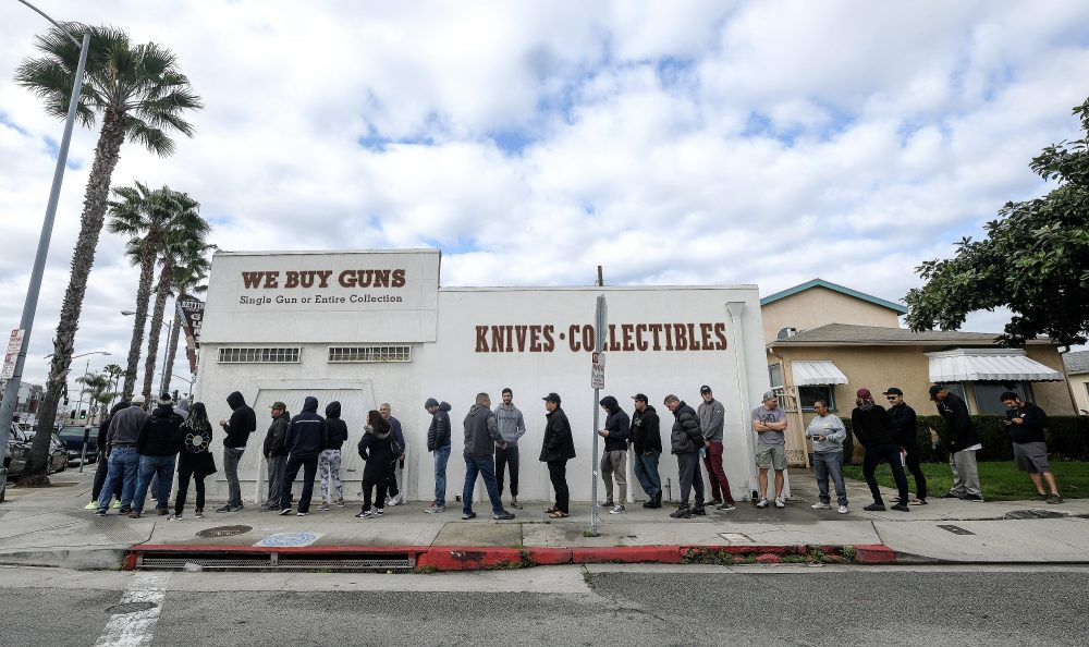 People wait in line to enter a gun store in Culver City, Calif., on Sunday. Coronavirus concerns have led to consumer panic buying of grocery staples, and now gun stores are seeing a similar run on weapons and ammunition.