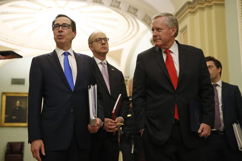 Treasury Secretary Steven Mnuchin, left, accompanied by White House Legislative Affairs Director Eric Ueland and acting White House chief of staff Mark Meadows, speaks with reporters as he walks to the offices of Senate Majority Leader Mitch McConnell of Kentucky on Capitol Hill in Washington on Tuesday.