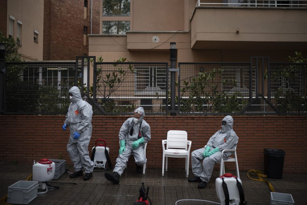 Firefighters wearing protective suits wait outside a nursing home before disinfecting it in efforts to prevent the spread of the new coronavirus Monday in Barcelona, Spain.