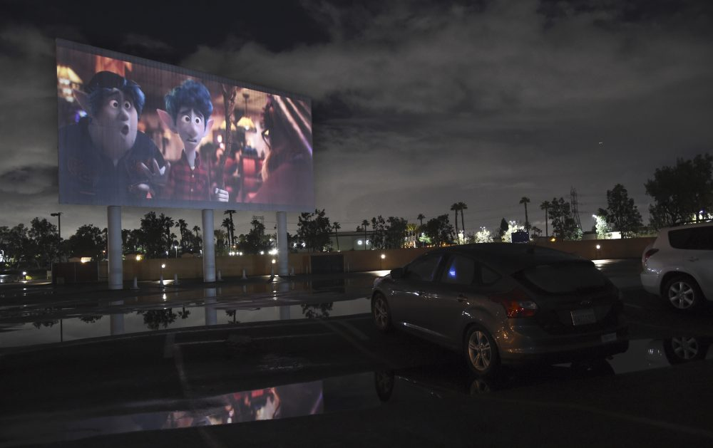 "Viewers in a parked car watch the animated film ""Onward"" on Thursday at the Paramount Drive-In Theatres in Paramount, Calif."
