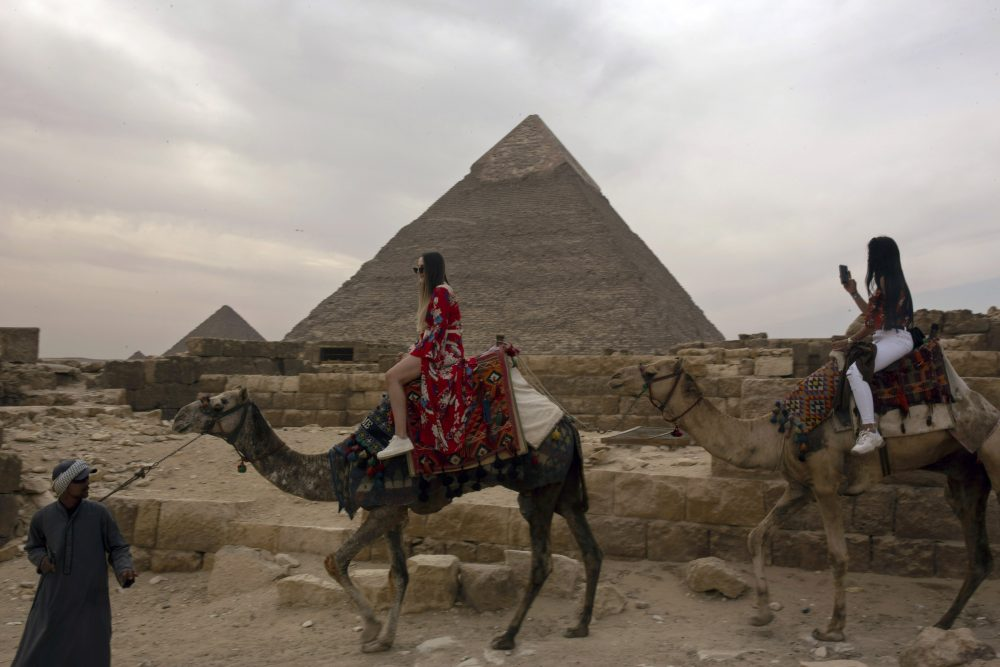 Two tourists ride camels at the Giza Pyramids near Cairo on March 10. The country's prime minister announced on Tuesday a two-week, 7 p.m. to 6 a.m. curfew for its over 100 million people to slow the spread of the new coronavirus.