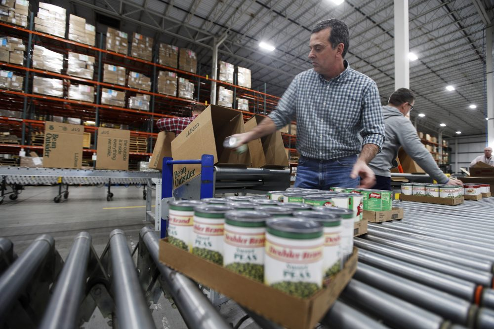 Mike Goodhartt and other workers at the L.L. Bean shipping center in Freeport box up donated foods Tuesday to be distributed to food pantries across the state. The outdoors retailer, which is experiencing sinking sales because of coronavirus, is partnering with the Good Shepherd food bank.
