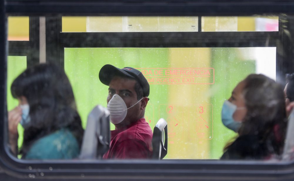 """Commuters wear masks Tuesday as they ride a bus in Mexico City. Mexico's government has broadened its shutdown of """"non essential activities,"""" and prohibited gatherings of more than 50 people but the federal call to stay home remains voluntary with no talk of penalties."""