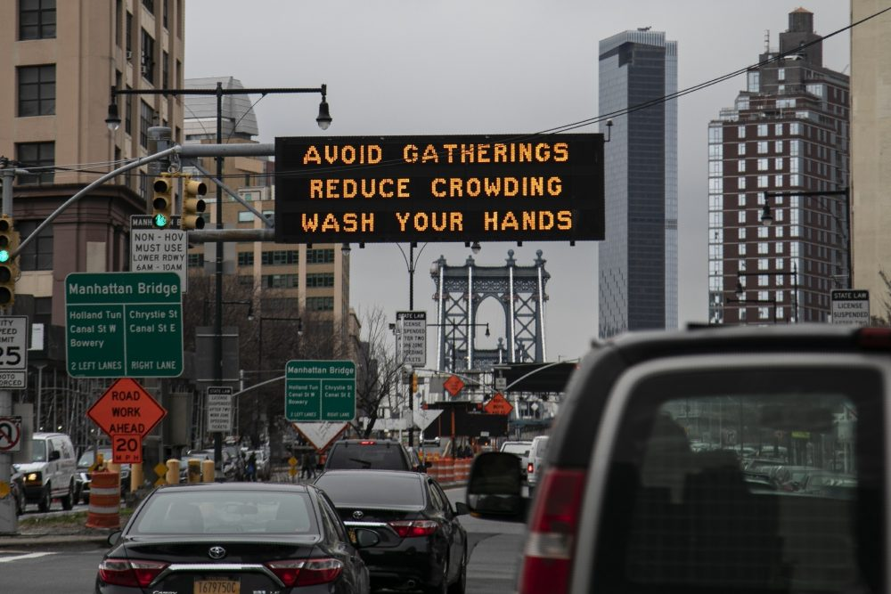 A flashing sign urges commuters headed for the Manhattan bridge  to avoid gatherings, reduce crowding and to wash hands in the Brooklyn borough of New York.