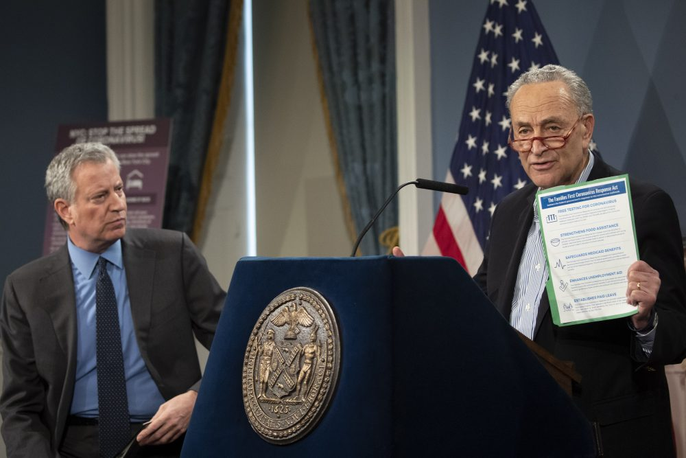 New York City Mayor Bill de Blasio, left, listens as Senate Minority Leader Sen. Chuck Schumer of New York speaks during a news conference on Saturday in New York. Congressional leaders are considering a host of measures to help businesses and people deal with the fallout of the coronavirus pandemic.