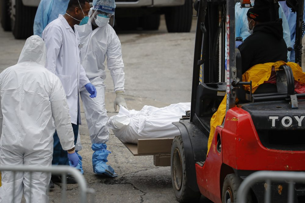 A body wrapped in plastic is prepared to be loaded onto a refrigerated container truck used as a temporary morgue by medical workers on Tuesday at Brooklyn Hospital Center in New York City.