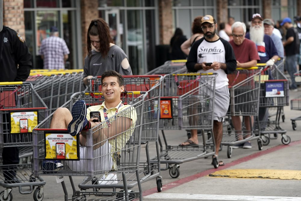 John Sinoski sits in a shopping cart while waiting for an H-E-B grocery store to open on Tuesday in Spring, Texas. Sinoski, who arrived around 6:30 in the morning, was near the front of a line of more than 150 people waiting to enter the store which opened at 8:00 a.m.