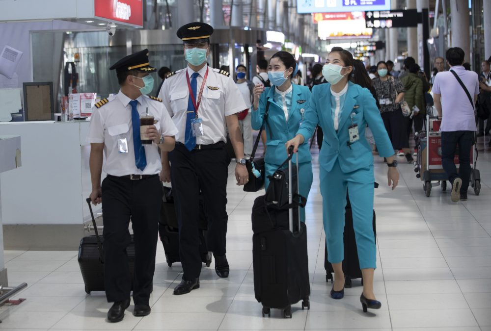 Flight crew wear protective masks as they arrive at the Suvarnabhumi Airport in Bangkok, Thailand, on Wednesday.