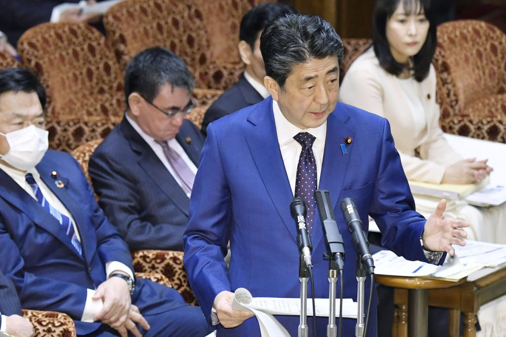 Japan's Prime Minister Shinzo Abe speaks at a parliamentary session in Tokyo on Monday. Abe said a postponement of the Tokyo Olympics would be unavoidable if the games cannot be held in a complete way because of the coronavirus pandemic.