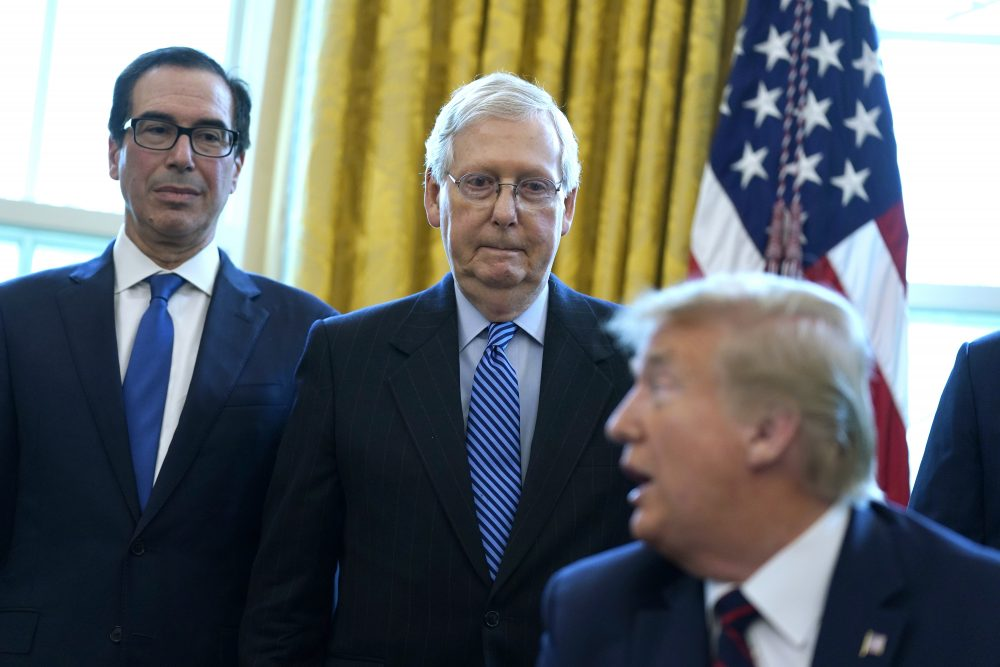 Treasury Secretary Steven Mnuchin and Senate Majority Leader Mitch McConnell, R-Ky., join President Trump  before he signs the coronavirus stimulus relief package in the Oval Office on March 27. McConnell said Republican Sen. Tom Cotton of Arkansas was among the first in Congress to raise an alarm about the virus.