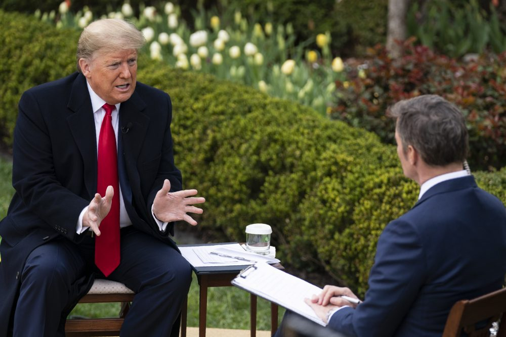 "President Trump talks with host Bill Hemmer during a Fox News virtual town hall with members of the coronavirus task force, in the Rose Garden at the White House on Tuesday. He said, ""We have to go back to work, much sooner than people thought."""