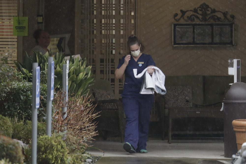 A worker at the Life Care Center in Kirkland, Wash., near Seattle, wears a mask as she leaves the building Monday. Several of the people who have died in Washington state from the COVID-19 coronavirus were tied to the long-term care facility, where dozens of residents were sick.