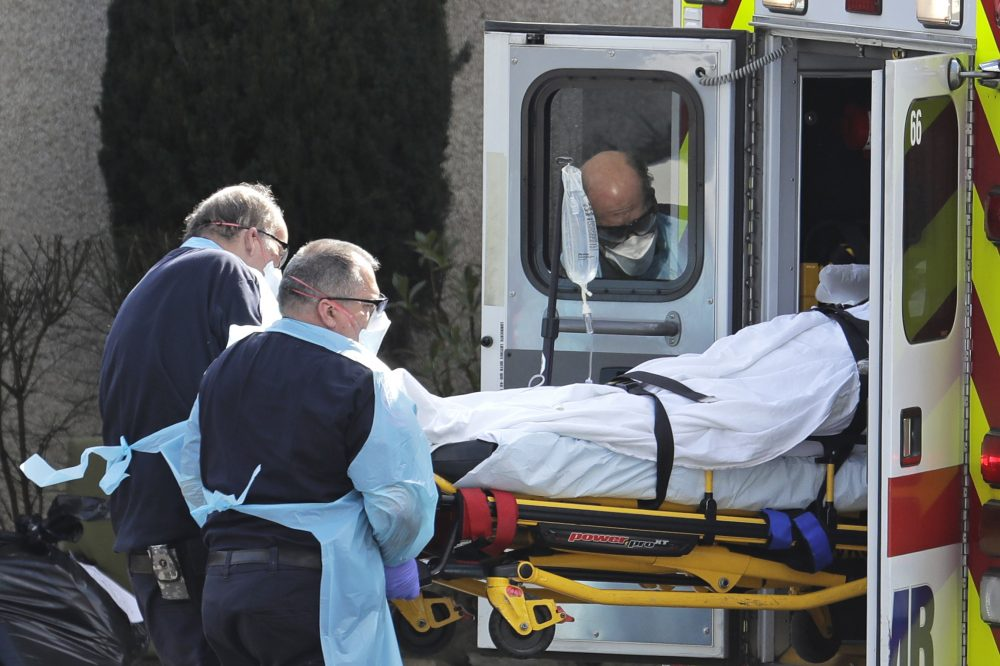 A person is loaded into an ambulance March 12 at the Life Care Center in Kirkland, Wash. The nursing home is at the center of the outbreak of the COVID-19 coronavirus in Washington state.