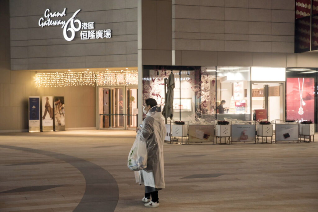 A pedestrian wearing a protective mask and rain coat stands in front of a shopping mall Feb. 12 night in Shanghai. Health officials say masks are not the most effective means of protecting against the coronavirus and should instead be worn by those who are already infected to prevent spreading the disease to others. Frequent and proper hand washing as well as social distancing practices are the best ways to stay healthy.