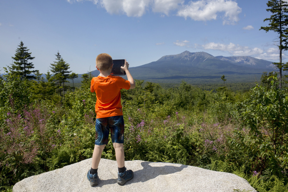 Sean Brady takes a photo of the view from the scenic lookout on the Loop Road in Katahdin Woods and Waters National Monument in 2017.
